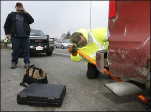 ODOT highway technician Brian Amos positions a jack under the rear of Joseph Riggs' disabled van, as Mr. Riggs calls a relative to explain he has help on the scene along I-475 at Central Avenue.