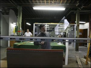 Tim Drouillard places a pane onto a cutting machine in the shop at Avondale Avenue and 11th Street.