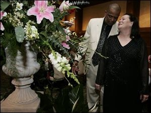 SAY IT WITH FLOWERS: Bruce Mason and his sweetheart, Rhonda Mrock-Parks, admire the towering flowers at the Toledo Club.
