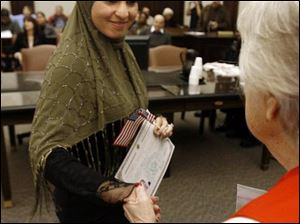 Rana Ahmad Jomaa Saleh, formerly of Lebanon, becomes a U. S. citizen with 67 other people from more than 30 countries during a ceremony in U.S. District Court in Tol