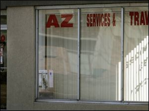 Justin Covyaw, manager of AZ Services & Travel, in the doorway of the business, said customers do not want to visit the office.