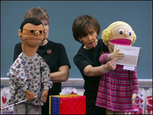 Kay Barbour, left, and Brenda Engle use puppets to teach students in Waterville Elementary School about mental and physical handicaps and how to accept them.