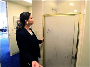 Amy Finkbeiner, the wife of Mayor Carty Finkbeiner, points out the shower stall on the 22nd floor of One Government Center that has led to heated criticism of her husband. The mayor says the shower will enable him to save time by showering at work after
