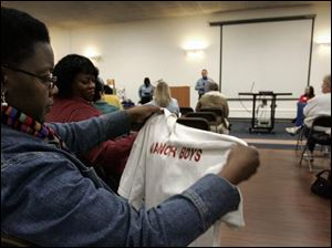 Yulanda McCarty-Harris looks over a Manor Boys gang T-shirt during the 6th annual Parents' Summit at Waite Brand Auditorium on Summit Street. About 75 parents attended the event.