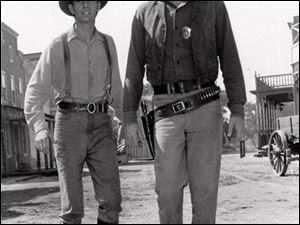 "Dennis Weaver, left, as deputy Chester, stands with James Arness as Marshall Matt Dillon in  the TV western ""Gunsmoke"" in 1956."