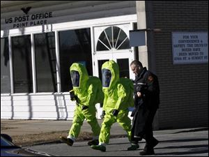 Firefighters in HAZMAT suits monitor the air outside the post office in Point Place.