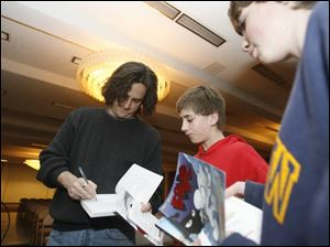 Cartoonist and author Jeff Smith signed autographs for Matt Kautz, 12, before speaking at the Stranahan Theater. Smith was the