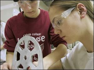 Samantha Mozena and Rachel Becker, from left at left, work on the robot's ball-shooting mechanism. The robotics regional competition starts tomorrow at Eastern Michigan University. The students have been working long hours.
