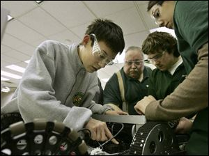 Toledo Technology Academy student Samuel Martin, left, works on the drive train of his team's robot. With him are teacher Tom McNutt and students Patrick Berning and Ericka Bilby, who also attend TTA.