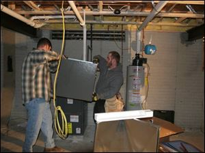 Matthew Lesti, left, and Nick Gangelder install a furnace and air-conditioning unit that replaces the one stolen from a Dold Homes site.