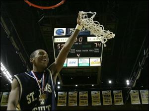 St. John's Jonathan Dunn displays the net after the Titans cut down the Scott Bulldogs last night at Savage Hall.