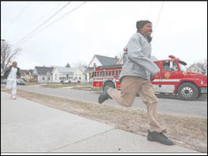 Devin Davis, 13, sprints home from school as firefighters patrol the area, part of a new effort with police after three recent reports of attempted child abductions.