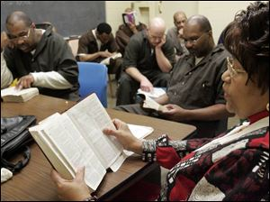 Diann Revels, an ordained minister, leads inmates during Bible study at the Lucas County jail. Some 35 volunteers with the Lucas County Jail Chaplaincy Committee conduct more than 20 Bible studies and church services each week.