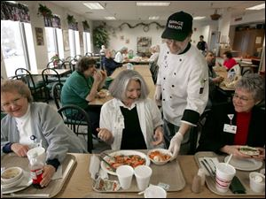 Chef Ray Hohman delivers a dessert of flaming pears to Linda Barbour, center, dining with friends Gloria Instone, left, and Shirley Pickering at Wood County Hospital.