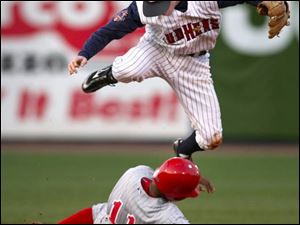 The Mud Hens  Kevin Hooper leaps over Scranton s Bobby Scales after tagging him out at second base.