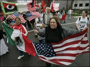 Lucy Dias of Detroit, left, and Yolanda Lopez of Toledo hold conjoined Mexican and American flags during the Farm Labor Organizing Committee's annual march in South Toledo.