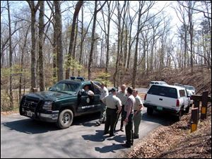 Offi cers from the Tennessee Wildlife Resources Agency gather near the Chilhowee campground where a black bear mauled three members of a family from Clyde, Ohio, on Thursday.