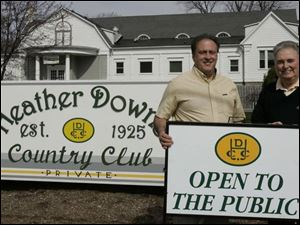 Joe Garverick, left, one of the new Heather Downs owners, and general manager Dan Hathaway show a sign of the times. The club, which opened in 1925, was private until this year.