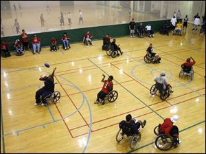 Red-shirted Crash players take on the University of Toledo football team on campus in a wheelchair football contest.