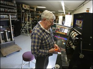 Paul Myers ponders a repair on a slot machine at the Delaware Avenue firm, which sells about 1,000 machines a year.
