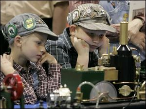 Young engineering hobbyists Robert Taylor, 7, left, and his brother, Nicholas, 9, sport a variety of identifier badges on their caps as they intently watch a model steam engine.