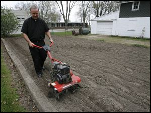 The Rev. Dennis Metzger of Holy Trinity Catholic Parish runs a tiller through his garden at the Assumption church.