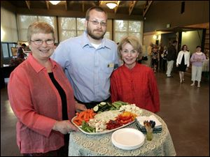 Judy Westmeyer, left, Chris Smalley, and Joanie Foster share hors d oeuvres in the Nature Preserve s Nature Center.
