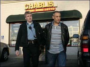 Guirguis Ragheb, right, is led from his store by Toledo police officer Jeff Jackson.