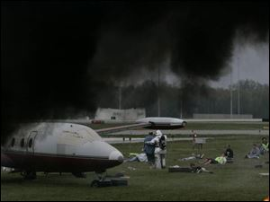 A pall of black smoke from diesel fires lends authenticity to this aircraft disaster drill at Toledo Express Airport. Rescue workers aid 'survivors' of a mock crash on the grass near a runway.