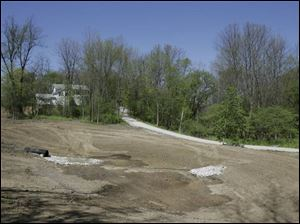 The white Lathrop House overlooks a ravine that has been cleared to make way for a pond in Sylvania.