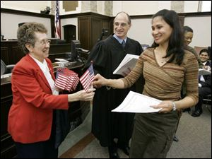 Ma Sylvia Arnino Adel, formerly of the Philippines, is the first new citizen to receive an American flag from Katherine Blystone of the Joseph Diehn American Legion Post as U.S. District Judge Jack Zouhary watches. Yesterday's ceremony was Judge Zouhary's first naturalization.