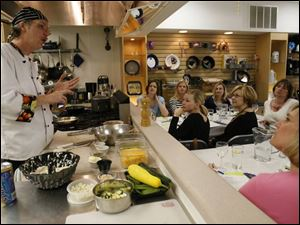 Chef Geoffery McKahan teaches a private cooking class to a mother's group at Essential Gourmet.