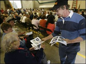 Cliff Moore, an Erie resident and fi refi ghter, passes out printouts of other developed intermodal rail yards during the meeting at the Erie Township Fire Department in Erie, Mich.