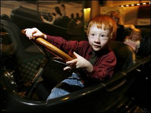 Trent Roseman, 4, of Curtice, Ohio, pretends to steer a 1917 Overland automobile at the Henry Ford Museum.