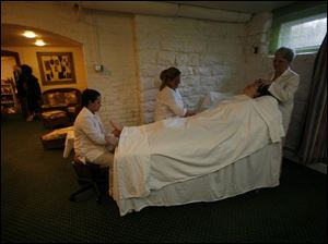 Patty Flanagan receives a simultaneous foot, hand, and scalp massage from Nikki Soto, left, Angie Sifuentes, center, and Jan Archambeau at The Kerr House in Grand Rapids, Ohio.