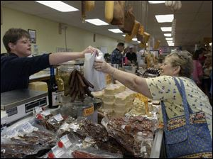 Janet Reid, left, hands a purchase to Nancy Pratt of London, Ohio, at Cheese Haven near Port Clinton. The shop sells 125 kinds of all-natural cheeses as well as 50 kinds of smoked meats.