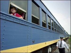 TLE&W chief Bill Linebaugh, strolls down the tracks next to the Waterville-based Blue Bird.