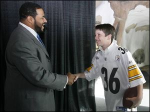 Jerome Bettis shakes hands with 13-year-old Steelers fan Reed Silverman of Toledo at the Toledo Zoo where Bettis was speaking.