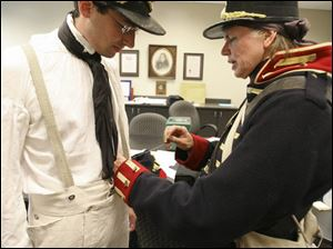 Tamia Land of Northwood sews suspenders into Blade staff writer Ryan E. Smith's uniform as he prepares for a re-enactment of Dudley's Defeat at Fort Meigs.