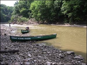 An Ohio Division of Natural Areas and Preserves canoe rests on a gravel bar in the upper Sandusky River during a recent scenic rivers get-acquainted trip.