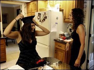 Jenny Kuhn tries on her cap for her 25-year-old sister, Jeana, before Perryburg High School's graduation on June 2. Jenny will attend Miami University in the fall.