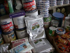 A grocery shelf at a bazaar shop contains foil packets of tuna and other smuggled American goods.
