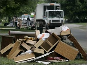 Piles of household items that were ruined in last week's storm await pickup as city crews make their way along Longwood Avenue in Toledo yesterday afternoon. Meanwhile, Gov. Bob Taft's office granted Lucas County emergency status, and city officials pledged continued help to the parts of the city hardest hit by the downpour.