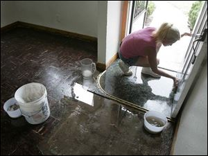 Sandy Wright cleans a home on Longwood Avenue, off Dorr Street. It was among many damaged in last week's storm.