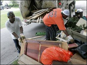 Toledo refuse collectors Michael Lee, left, and Eric Johnson pick up flood-damaged items from homes in South Toledo.