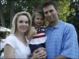 RED, WHITE, AND BABY BLUE: Katrina and Daniel Trombley hold daughter Isabella, 21 months, who shows off her patriotism at the Toledo Country Club picnic.