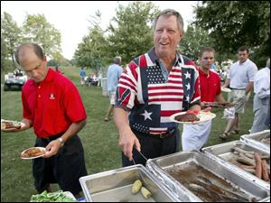 HEAPING HELPINGS: Dave Jagodzinski carries off two plates and Tom Tillander dives into the trays at the Belmont Country Club Fourth of July party. Although it seems that the food was nearly gone, the trays were refilled and Mr. Tillander had his share.