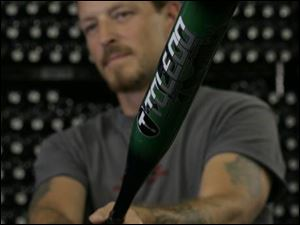 Dave Kidd, of Toledo Sports Equipment, lifts a Toledo brand Katana Dragon slow-pitch bat.