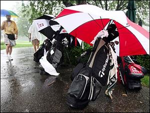 Clubs are left under cover as players head inside during a rain delay today at Highland Meadows Golf Club. Today's Pro-Am was cancelled.