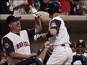 Mud Hens pitching coach Jeff Jones greets Ryan Raburn after Raburn hit a home run n the seventh inning for the International League in last night's Triple-A All-Star game.